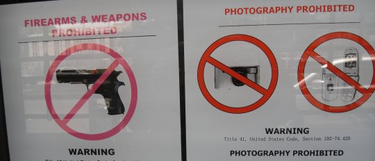 Photograph of 2 sigs: Weapons 			  prohibited and Photography prohibited